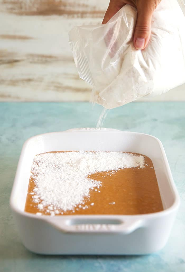Cake mix being sprinkled over pumpkin filling in a white baking dish.