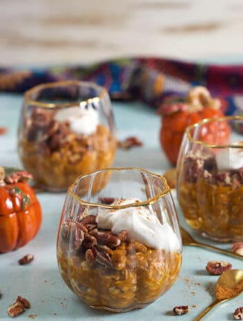 three glasses with pumpkin overnight oats on a blue background.