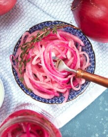 overhead shot of pickled red onions in a blue and white bowl on a white towel.