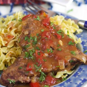 Close up of Swiss steak on a blue plate.
