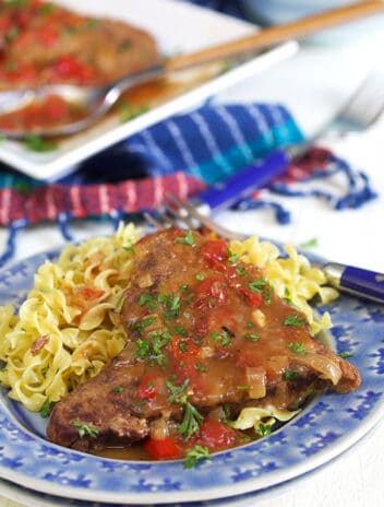 Swiss steak on a blue plate with egg noodles.