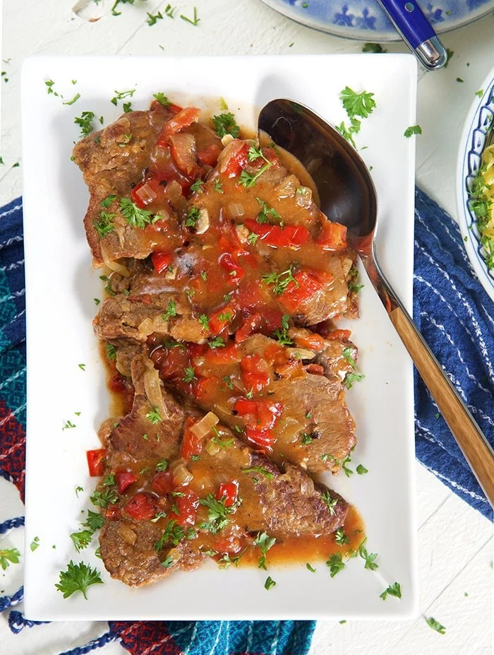 Overhead picture of Swiss steak on a white platter with a wooden spoon.