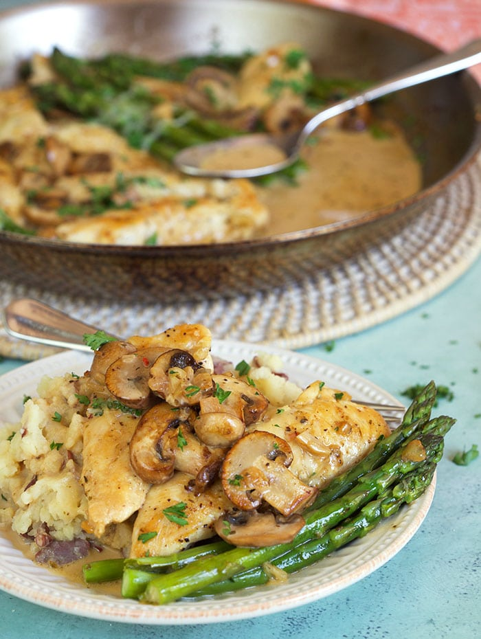 Chicken Madeira on a plate with asparagus.