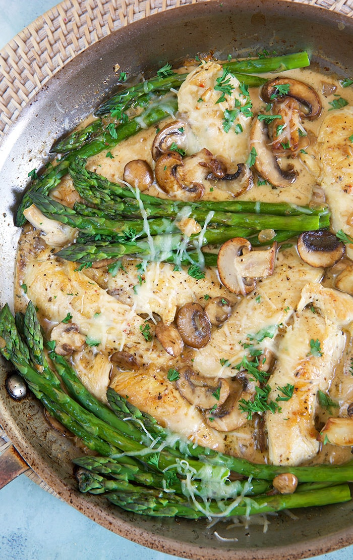 Cheesecake Factory Chicken Madeira in a skillet with asparagus.