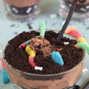 Dirt cake with gummy worms in a glass bowl with a spoon on a blue background.