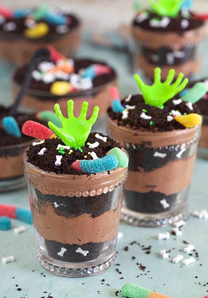 Dirt pudding cups in glasses with zombie hands.