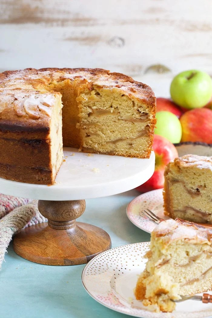 Jewish apple cake with two slices cut out and apples in the background.