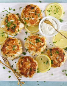 best crab cakes on a white platter with a bowl of tartar sauce.