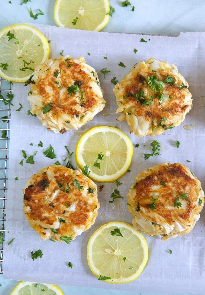 crab cakes on parchment on a cooling rack with lemon.