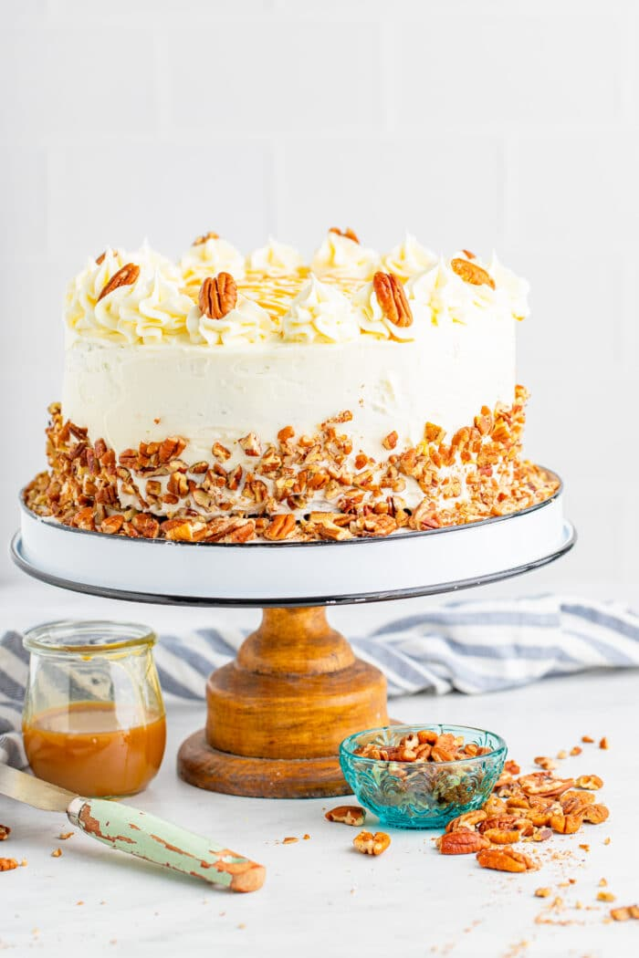 Bourbon Butter Layer Cake on a cake stand with caramel sauce in a jar.