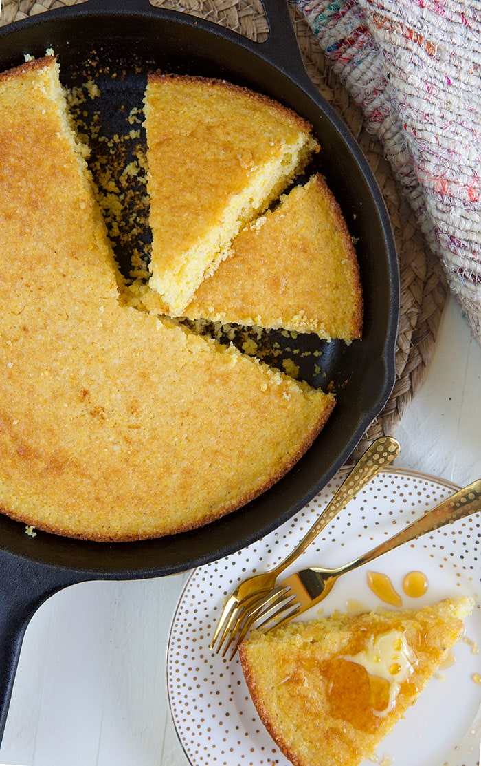 Two slices of cornbread are in a skillet, next to the uncut cornbread.