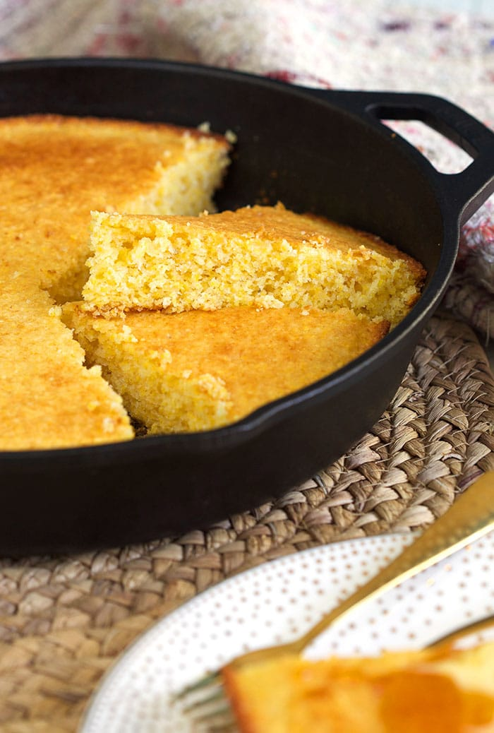 Cornbread is sliced in pieces in a black skillet.