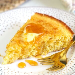 A piece of cornbread is garnished with butter and honey on a white plate.