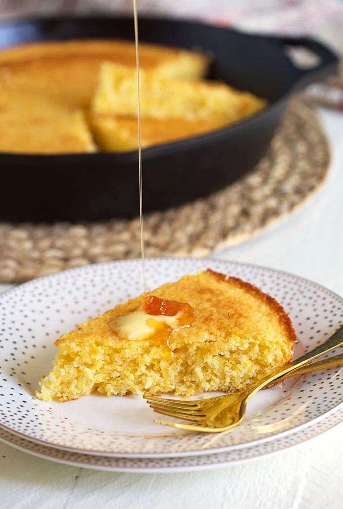 Honey is drizzled onto a piece of cornbread.
