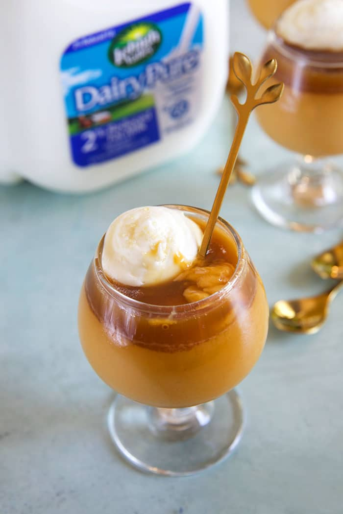 Butterscotch Pot de Creme in glasses on a blue board with a gallon of milk in the background.
