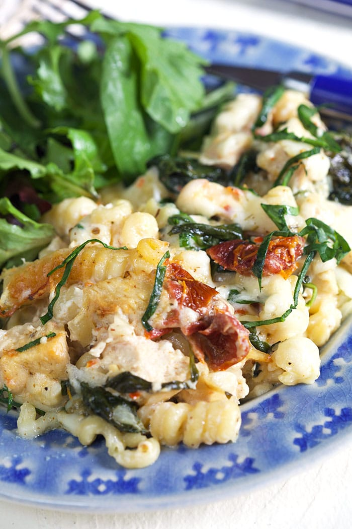 Chicken Florentine Pasta on a blue plate with a salad.