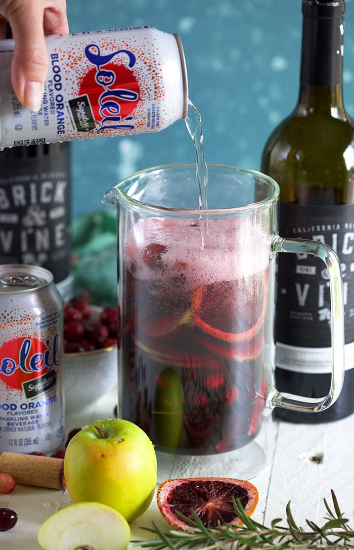 Sparkling water being poured into a pitcher with wine and fruit to make sangria