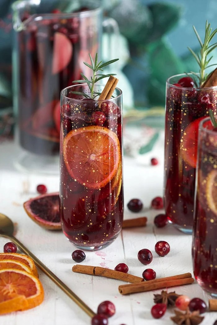 three glasses filled with Christmas sangria on a white background.