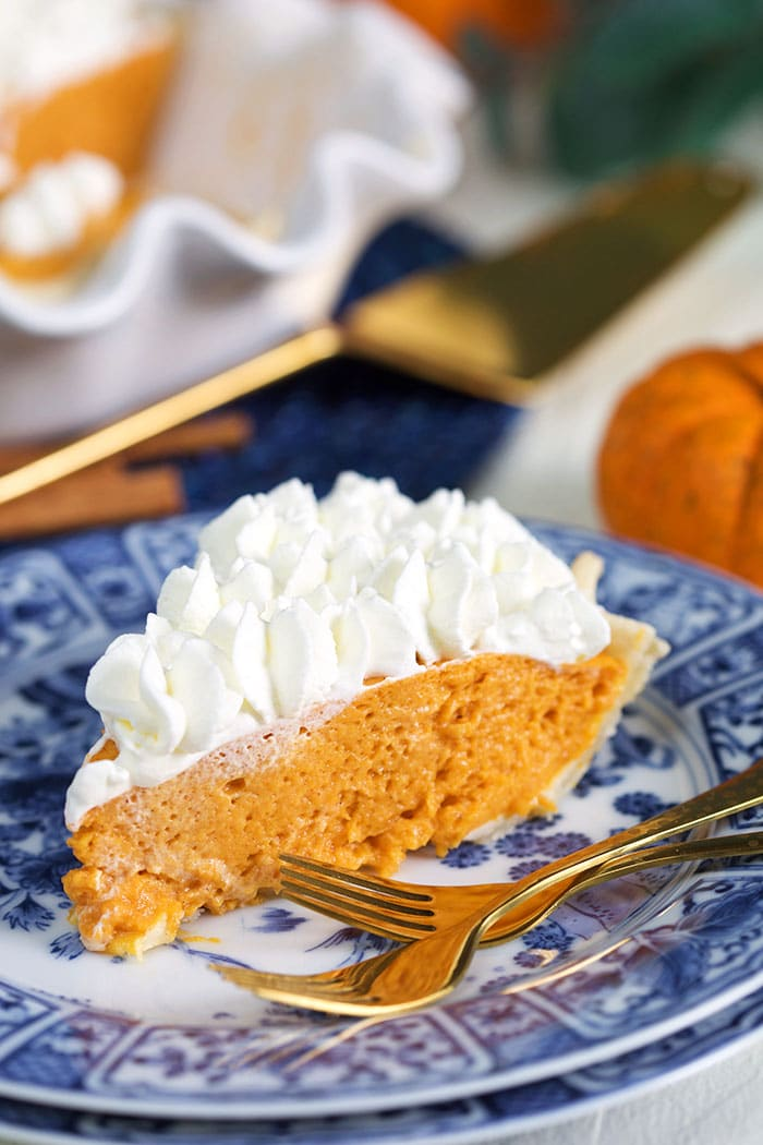 Slice of Pumpkin chiffon pie on a blue and white plate.
