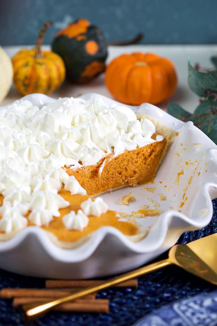 Pumpkin chiffon pie in a white pie plate with pumpkins in the background.