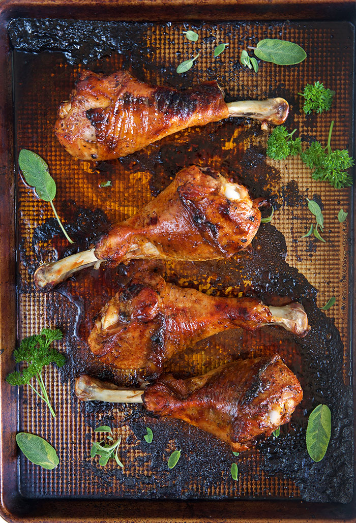 Four roasted turkey legs are on a baking sheet.