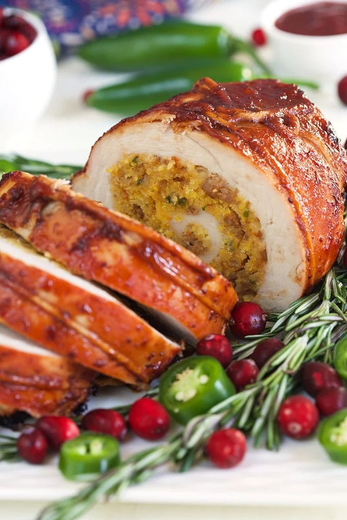 Turkey Roulade sliced on a white platter with rosemary and cranberries.