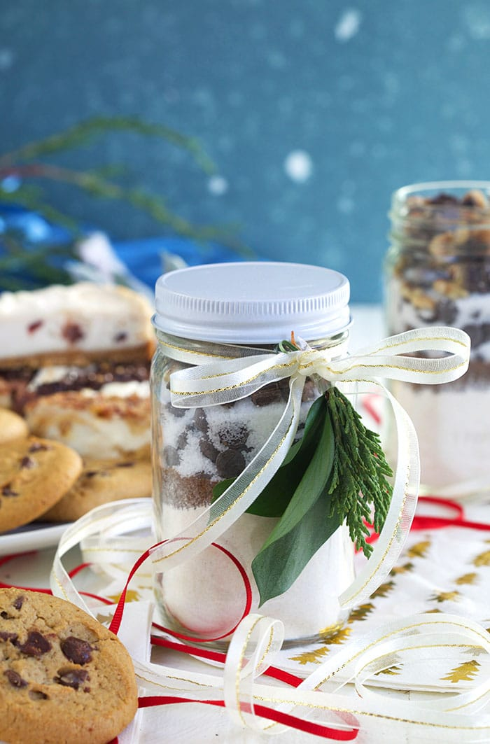 Cookie Mix in a Jar with a ribbon and evergreen fronds tied to the front.