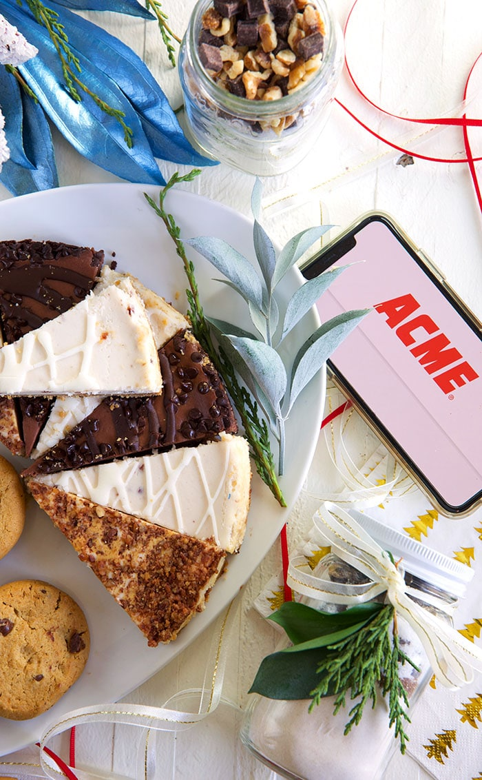 cheesecake on a white platter with an iPhone with the ACME logo