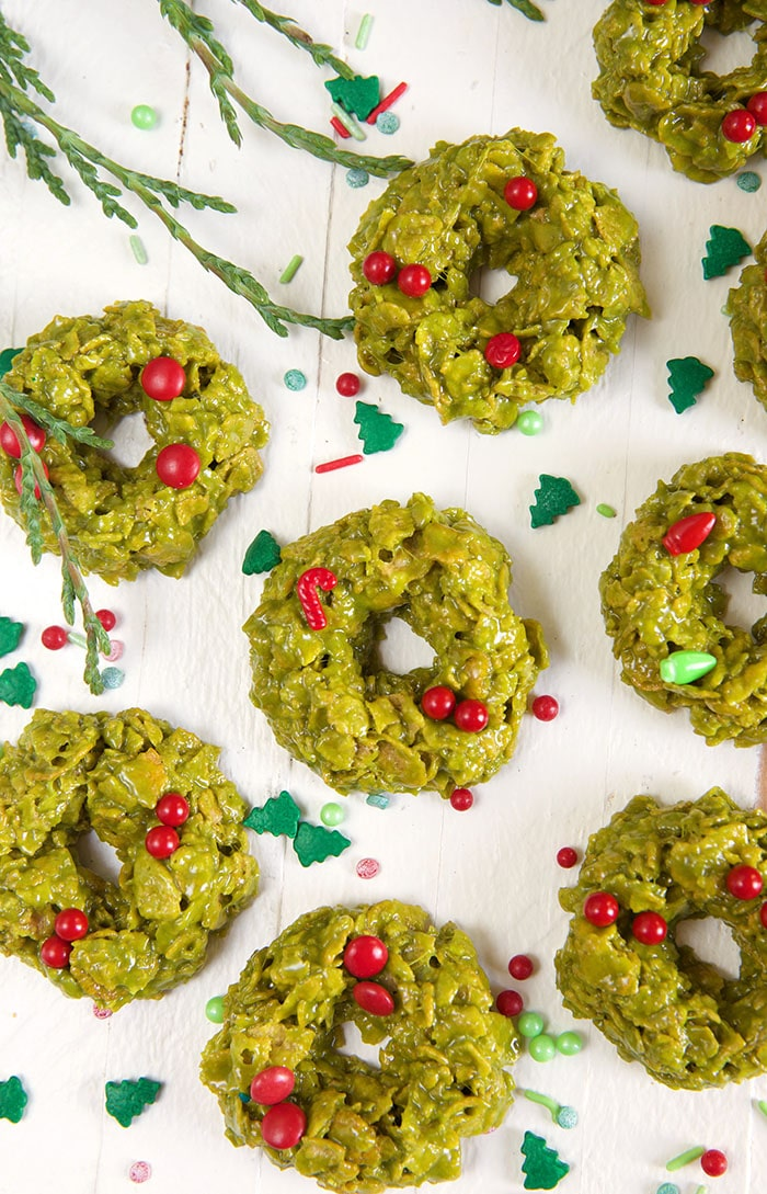 Multiple green cornflake wreath cookies are spread out on a white surface.