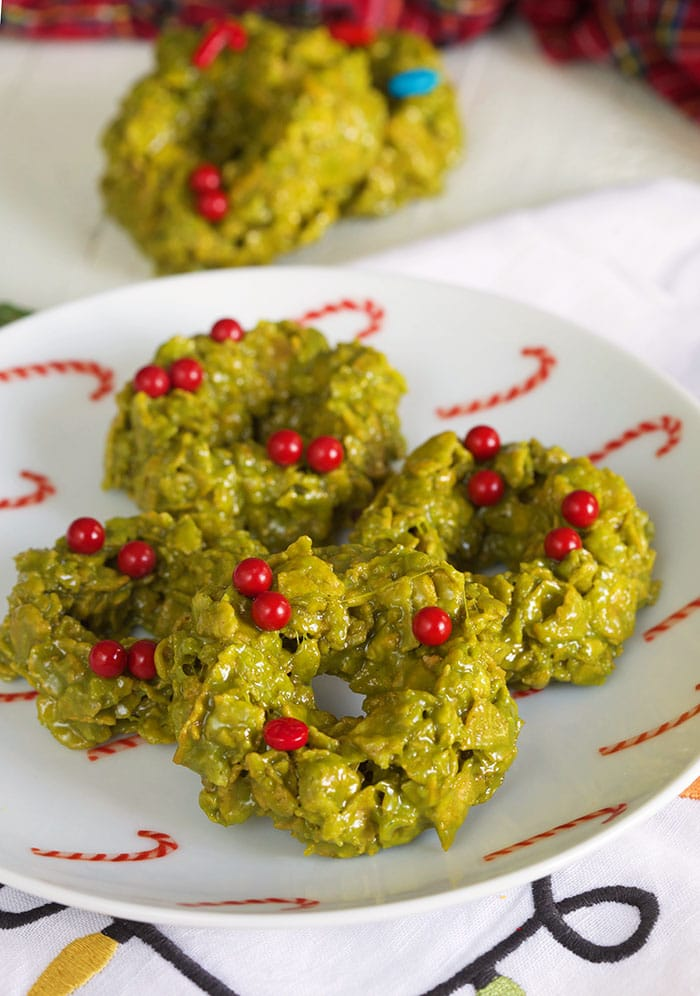 Four green Christmas cookies are on a white plate.