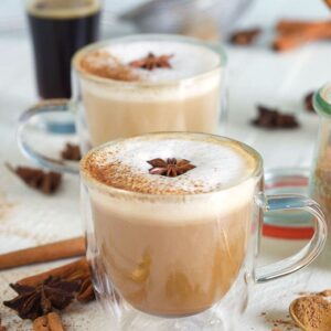 White frothy cream sits on top of two brown lattes.