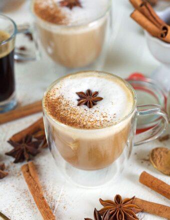 Cinnamon stick sit around a glass mug of chai tea.