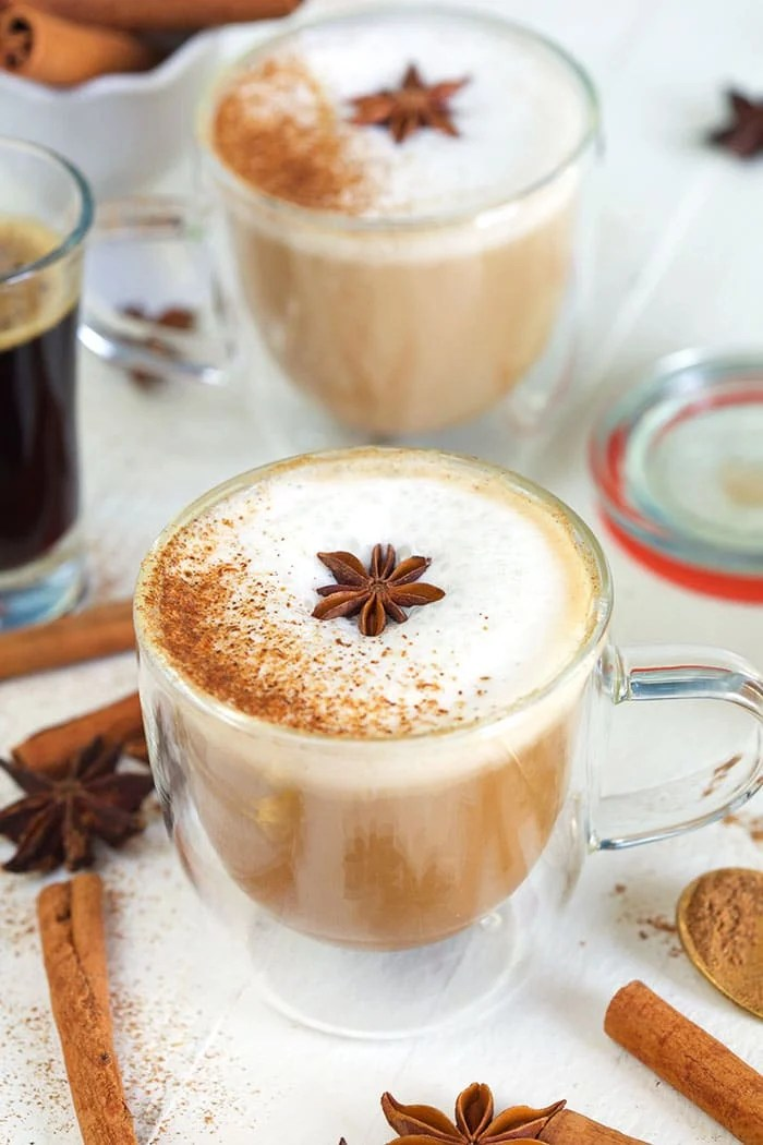Two chai lattes are garnished with star anises in glass mugs.
