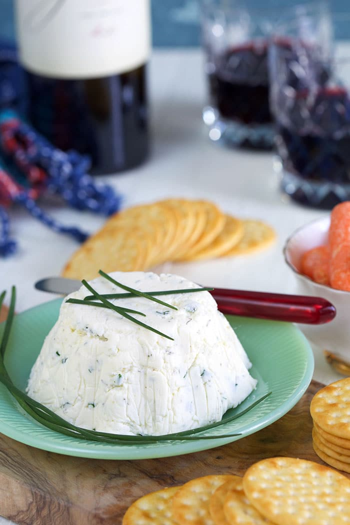 Boursin cheese is garnished with fresh chives.