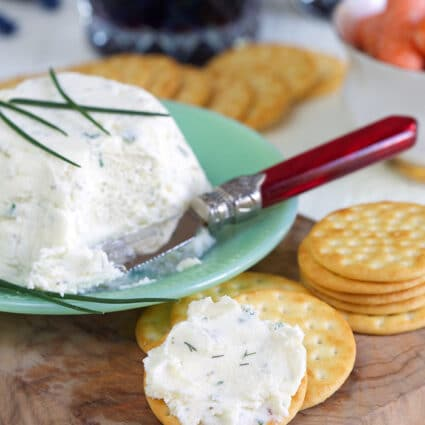 White creamy cheese is spread on a cracker.