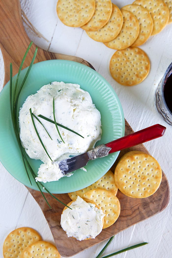 A blue bowl contains a large serving of Boursin cheese.