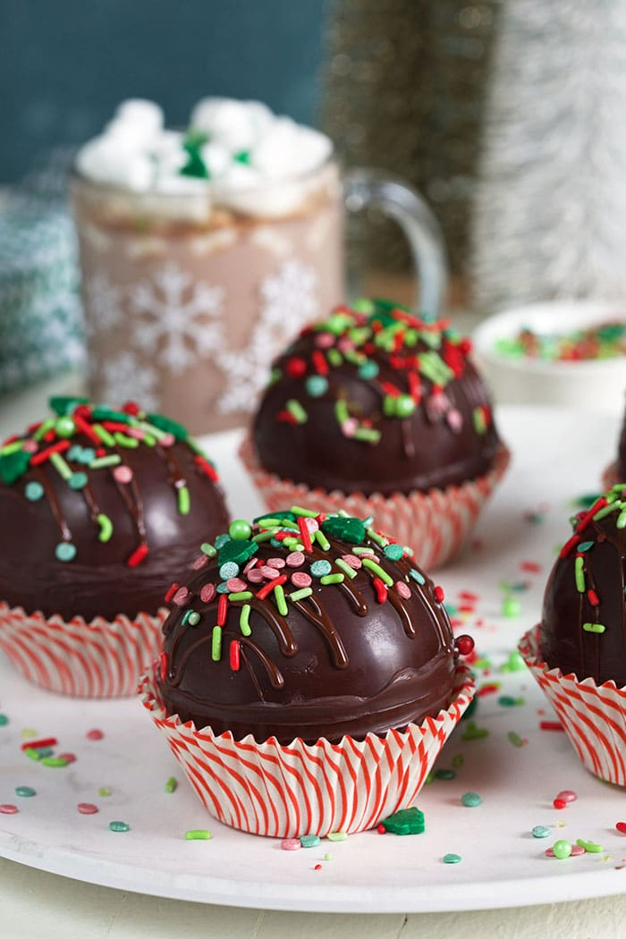 Hot chocolate bombs on a marble plate in red and white cupcake wrappers.