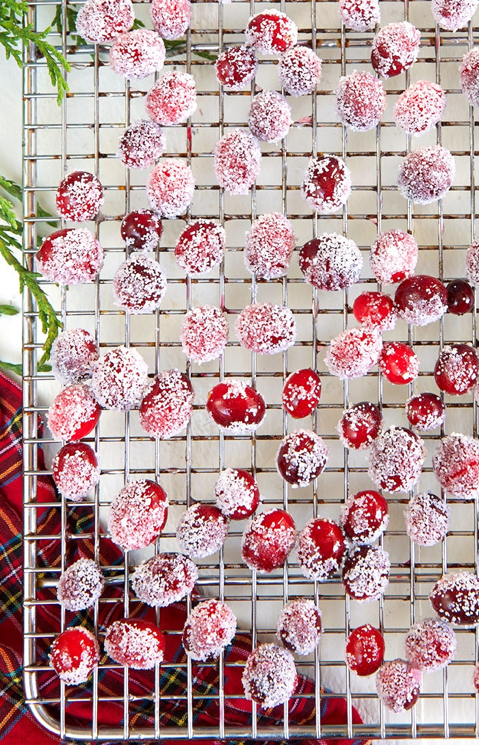 Sugared cranberries on a cooling rack on a white background.
