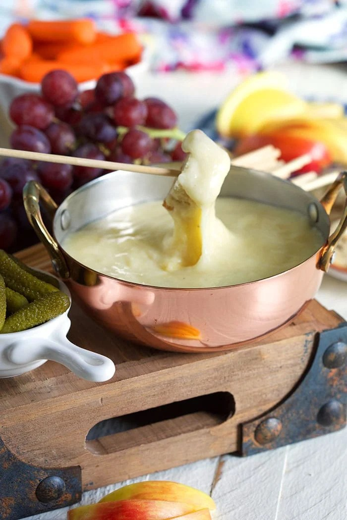 bread being dipped into fondue in a copper pot.