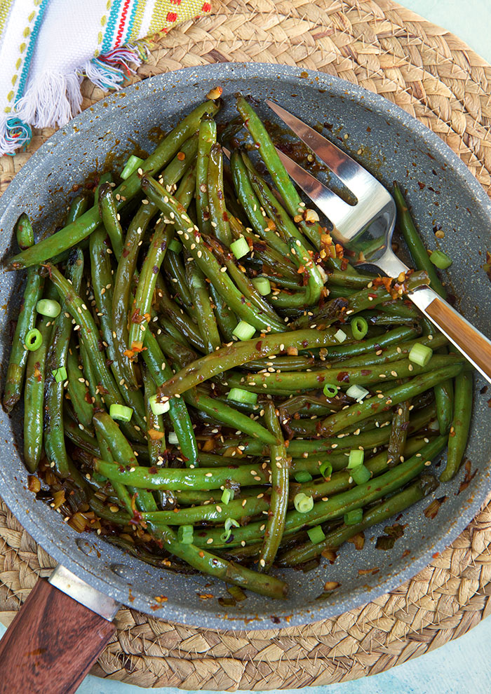 A large serving fork is in a serving of green beans.