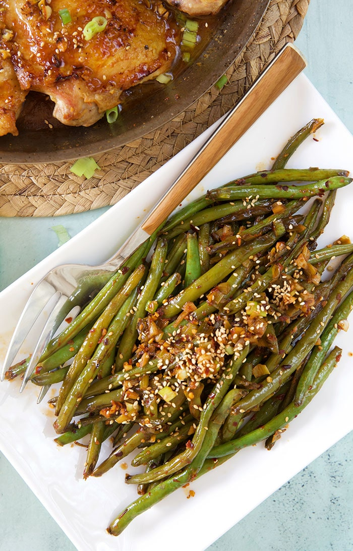 A serving of Szechuan green beans is presented on a white plate next to a serving of orange chicken.