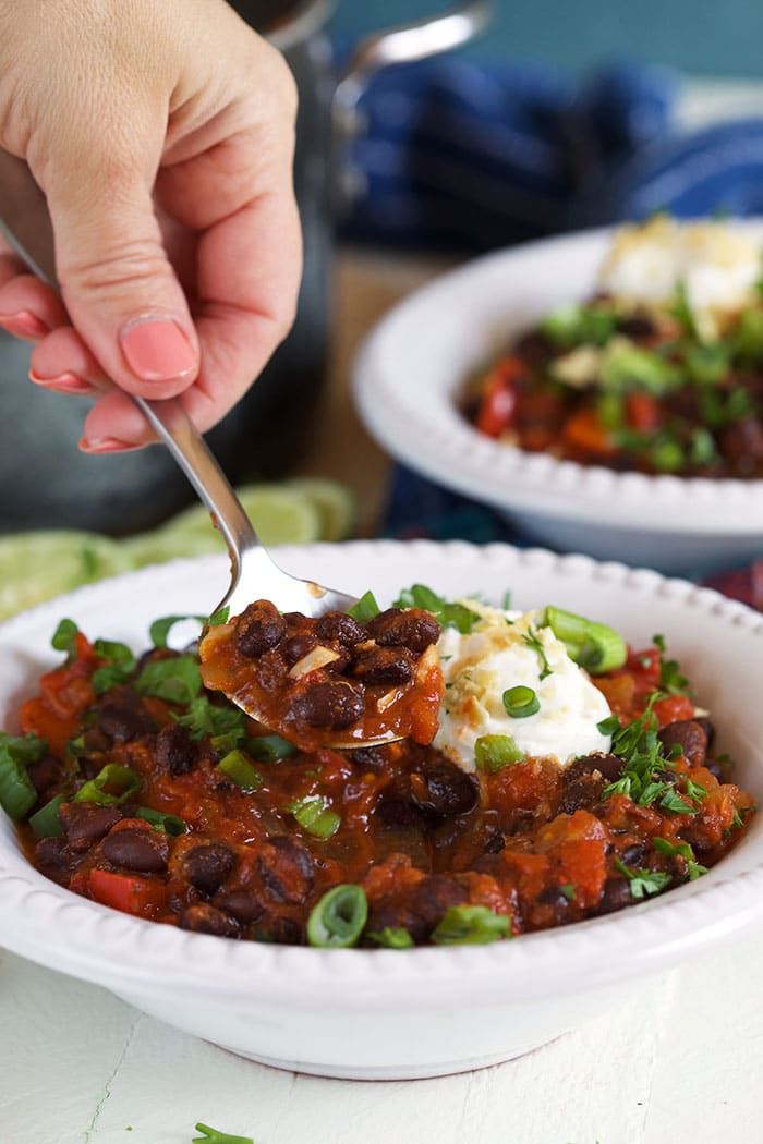 A spoonful of chili is scooped out of a white bowl.