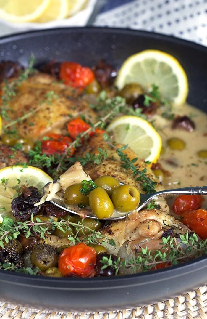A spoon is holding several green olives above a skillet full of chicken provencal.