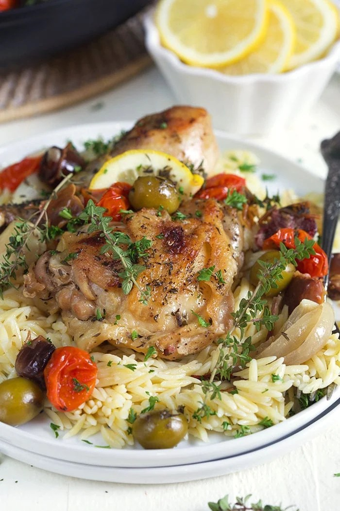 Roasted chicken, olives and herbs sit atop a serving of rice on a white plate.