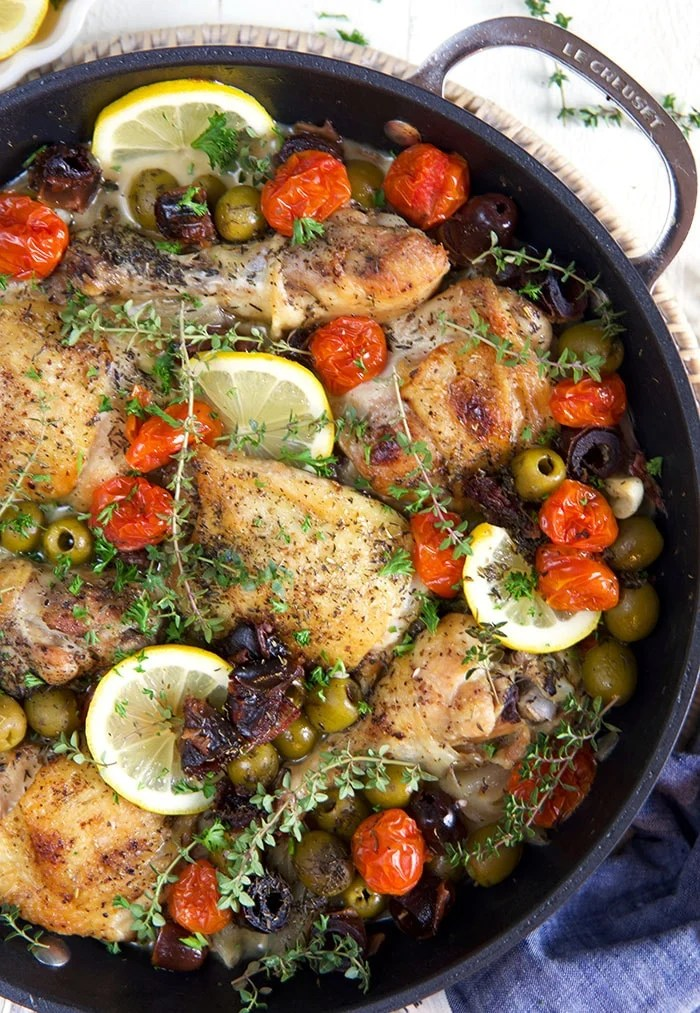 Chicken thighs, lemons and olives are prepared in a large black skillet.