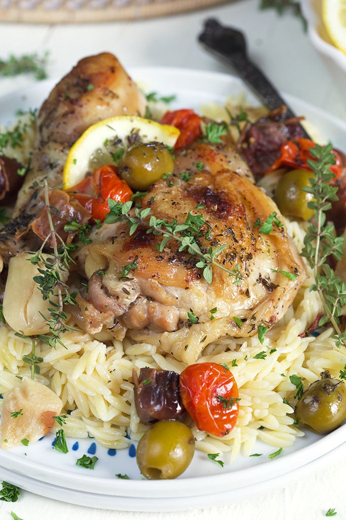 A plate of roasted chicken, herbs and rice is ready to be eaten.