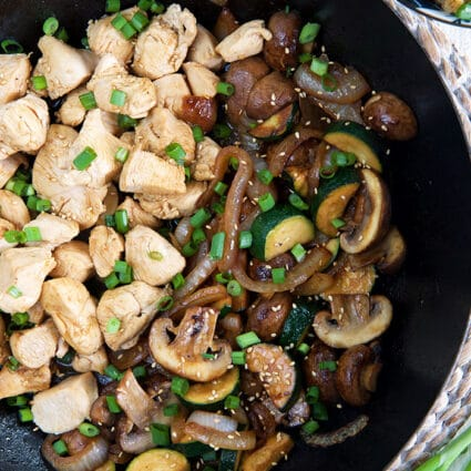Chicken and veggies are in a large skillet, garnished with chopped green onions.