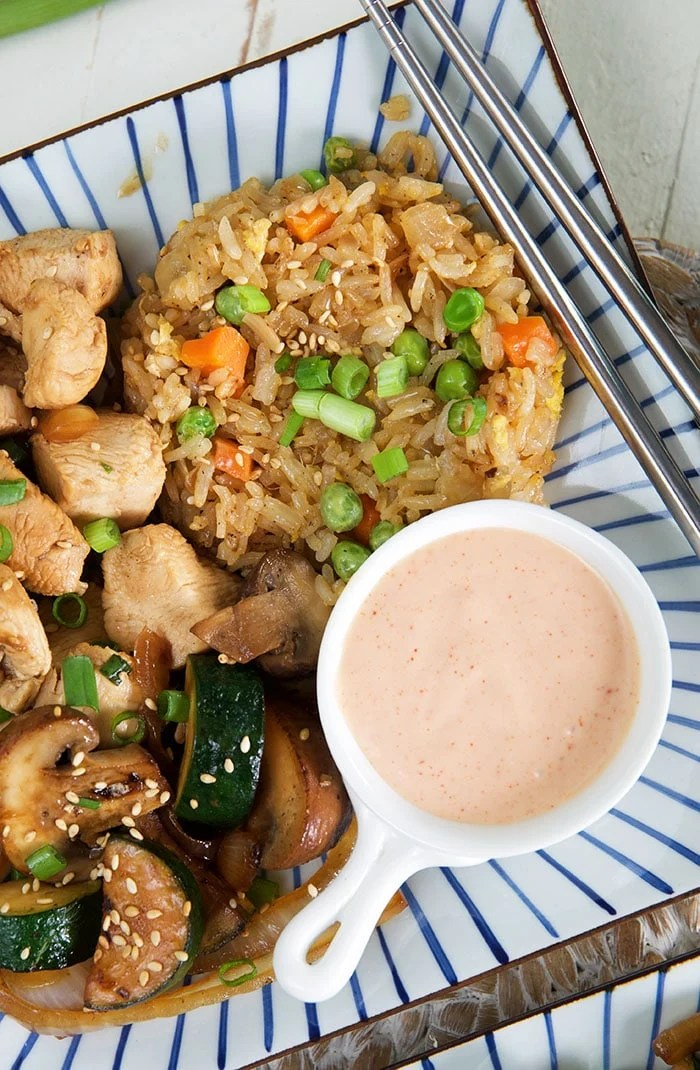 Fried rice is served with yum yum sauce and hibachi chicken.