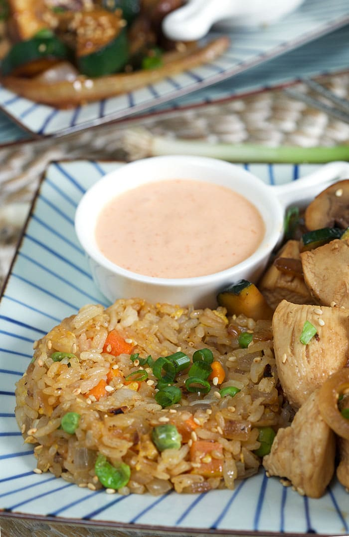 Hibachi fried rice and yum yum sauce are served on a striped plate.