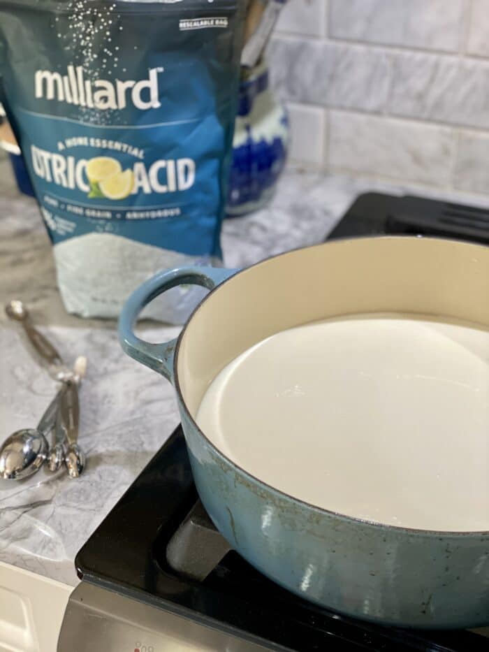 A large blue pot is heating milk on an oven, next to a bag of citric acid.